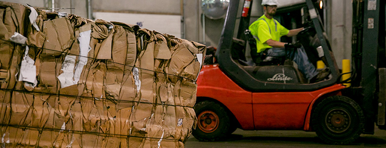 A bundle of recycled cardboard with a forklift in the background.
