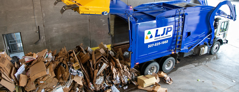 An LJP waste collection truck unloading recycled cardboard.