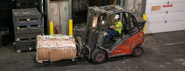 A forklift carrying a bundle of recycled cardboard.